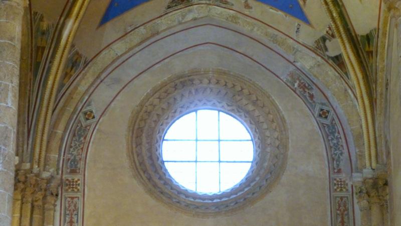 Elegante occhio di stile lombardo, eseguito con la stessa tecnica di intaglio delle modanature presenti nell'Abbazia dei Santi Severo e Martirio e nel Palazzo del Popolo